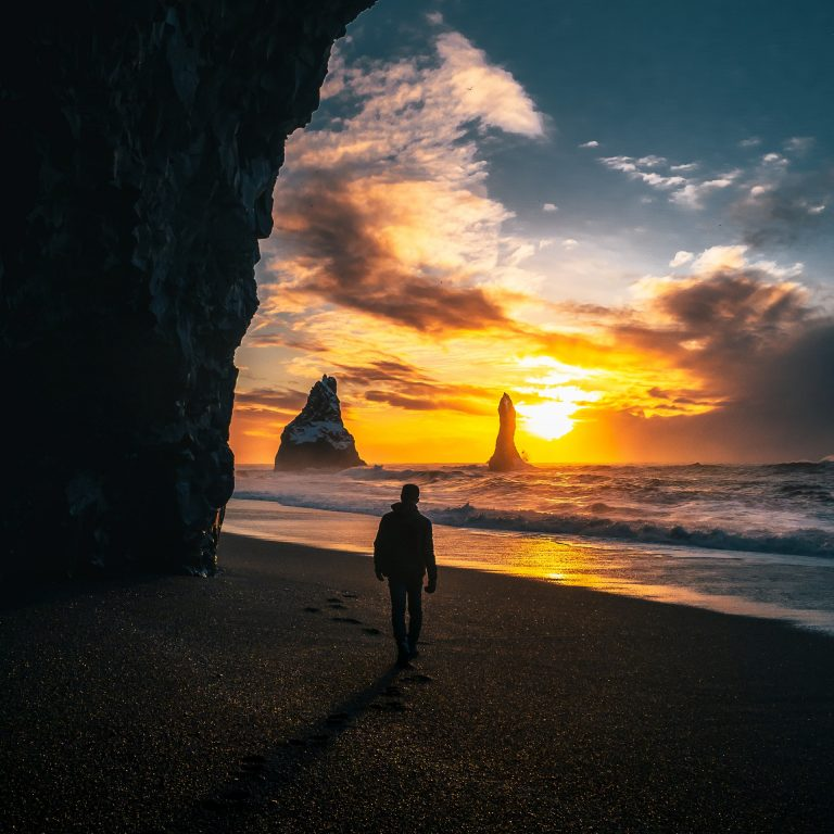 photo-of-person-standing-on-seashore-during-golden-hour-3380805